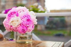 Charming bouquet of peonies in vase on table at Royalty Free Stock Photos