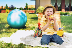 Charming boy eating huge apple Stock Photos