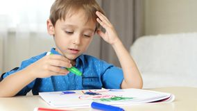 Charming boy of preschool age sitting at a table in his room. Happy child spends time drawing bright markers in the stock video footage