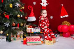 Charming boy sits on a sleigh next to a lot of presents Royalty Free Stock Photo