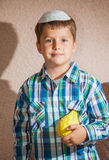 The charming boy in white festive skullcap holds etrog. The charming seven-year-old boy in a white festive skullcap holds citrus in hand. The etrog - ritual Royalty Free Stock Images