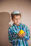 Charming boy in white kippah is holding citron Royalty Free Stock Image