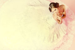 Charming bride. Beautiful charming bride in a luxurious dress looking up. Over pink background Stock Images