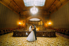 Charming bride dancing with handsome elegant groom near old wooden baluster on the background of luxury interior Stock Photo