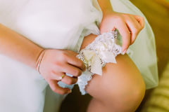 Charming bride dressing bridal garter indoors. Close-up woman arms Stock Photo
