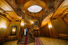 Charming bride and elegant groom kissing on luxurious vintage wooden stairs with the background of classic interior Stock Images