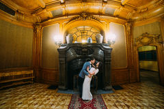 Charming bride and elegant groom at luxurious vintage classic interior have a romantic moment near fireplace Stock Photo