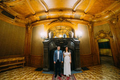 Charming bride and elegant groom at luxurious vintage classic interior posing in front of fireplace Royalty Free Stock Image