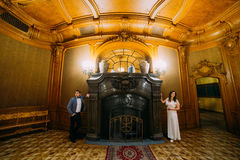Charming bride and elegant groom at luxurious vintage classic interior posing near fireplace Royalty Free Stock Photo