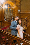 Charming bride and elegant groom on luxurious vintage wooden stairs with the background of classic interior Stock Images