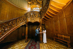 Charming bride and elegant groom under luxurious vintage wooden stairs with the background of classic interior Royalty Free Stock Photo