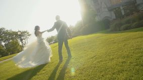Brunette bridal woman spinning with handsome man on the green grass and enjoying with each other stock footage