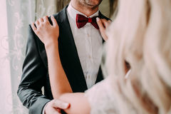 Charming bride fixes red bow tie on groom`s neck while they stand near the window. Wedding. Charming bride fixes ornamented red bow tie on groom`s neck while Stock Photography