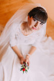 Charming bride in gorgeous white dress waiting for her wedding posing with cute floral boutonniere Stock Image