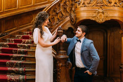 Charming bride and handsome elegant groom lovingly looking on each other near old wooden stairs with the background of Stock Image