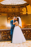 Charming bride and handsome elegant groom near old wooden baluster with the background of luxury interior. Charming bride and handsome elegant groom near old stock image