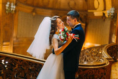 Charming bride and handsome elegant groom near old wooden baluster with the background of luxury interior. Charming bride and handsome elegant groom near old stock photography