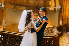 Charming bride and handsome elegant groom near old wooden baluster with the background of vintage interior. Charming bride and handsome elegant groom near old stock image