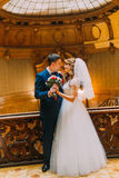 Charming bride and handsome elegant groom near vintage wooden baluster with the background of luxury interior Stock Photos