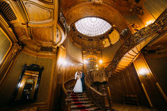 Charming bride and handsome elegant groom on old wooden stairs with the background of luxury interior Stock Images