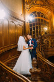 Charming bride and handsome elegant groom on old wooden stairs with the background of vintage interior Royalty Free Stock Photo