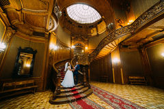 Charming bride and handsome elegant groom posing on a background of astonishing vintage interior Royalty Free Stock Photo