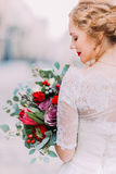 Charming bride with long hair looks on her wedding bouquet (back view) Stock Images