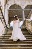 Charming bride in long white wedding dress and floral wreath going down by antique palace stone stairs Royalty Free Stock Images