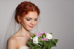 Charming bride looks at a bouquet Royalty Free Stock Photo