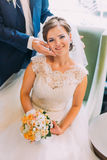 Charming bride sits in chair holding wedding bouquet and loving groom stands near stock photos