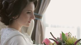 Charming bride sitting in the chair with the wedding bouquet in the hands stock video footage