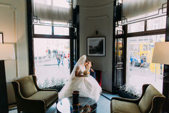Charming bride sitting on knees of her lovely groom in a luxurious interior with shiny windows as background Royalty Free Stock Photos