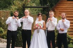 Charming bride stand by the groomsman on the backyard.  stock photo