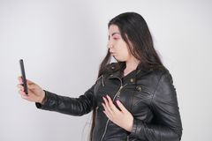 Charming brunette in black leather jacket in rock style stands with a smartphone on a white background in the Studio stock image
