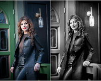 Charming brunette in black leather outfit with green painted door on background. Sexy gorgeous young woman with long curly hair Stock Photos