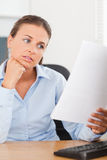 Charming brunette businesswoman looking at a paper Royalty Free Stock Photography