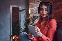 A charming brunette in casual clothes with a tablet and headphon Stock Photography