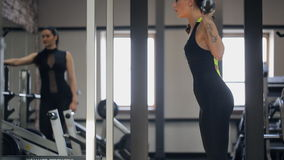 Charming brunette does squats with bar. stock video