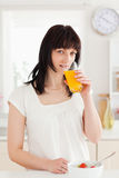 Charming brunette drinking a glass of orange juice Stock Images