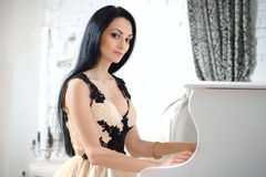 Charming brunette in evening dress playing the piano. Stock Image