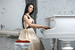 Charming brunette in evening dress playing the piano. Stock Photography