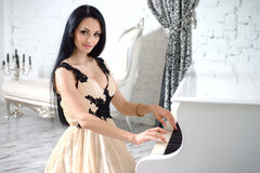 Charming brunette in evening dress playing the piano. Stock Photo