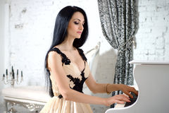 Charming brunette in evening dress playing the piano. Royalty Free Stock Photos