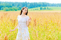 Charming brunette in a field of yellow flowers Royalty Free Stock Photo
