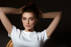 Charming brunette girl with bunched hair dressed in white t-shirt and jeans poses on the black background in the studio.  stock images