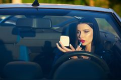 Charming brunette girl paints lips in a convertible car with natural soft light. Empty space royalty free stock image