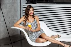 Charming brunette girl in a wonderful gray evening dress is sitting in a stylish white chair with a glass of juice royalty free stock image