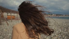 Funny woman is smiling broadly at camera, catching hat from hard wind, portrait. Charming brunette lady is laughing, looking at camera, walking on pebble beach stock video footage