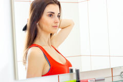 Charming brunette lady posing in front of mirror. At the bathroom stock photography
