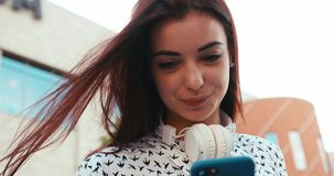 Charming brunette lady with pretty smile is chatting on the mobile phone outdoor. Up portrait. 4k footage. Charming brunette lady with pretty smile is chatting stock video